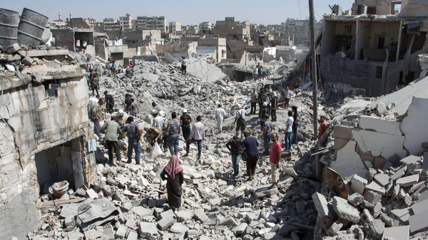 Syrians stand on the rubble of buildings after a missile fired by Syrian government forces hit a residential area in the Maghayir district in the old quarter of the northern Syrian city of Aleppo on July 21, 2015. According to the Syrian Observatory of Human Rights more than 35 homes were destroyed in the attack killing at least 18 civilians, adding that the death toll was likely to rise. AFP PHOTO / KARAM AL-MASRI